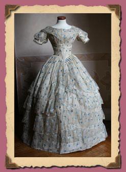 Abito da ballo intero in taffetas color avorio ricoperto di velo di seta  avorio ricamato a fiorellini azzurri e blu. 9740a9e1397